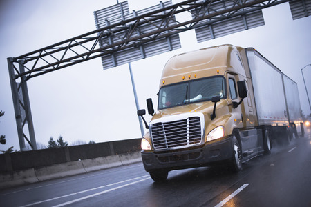Brown modern big rig semi truck popular among drivers truckers going to long haul commercial cargo  driving on a wet road in the rain with headlights for safe driving and reflection of lights. Stockfoto