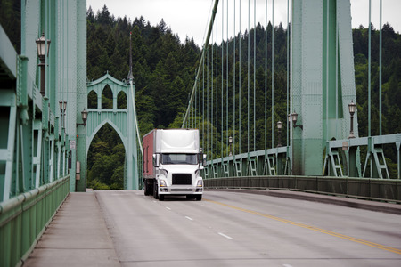 long johns: Semi Truck with a box trailer moving on the picturesque gothic riveted metal bridge with arches and cable extensions. St. Johns Bridge is located in Portland Oregon and is a local landmark Stock Photo