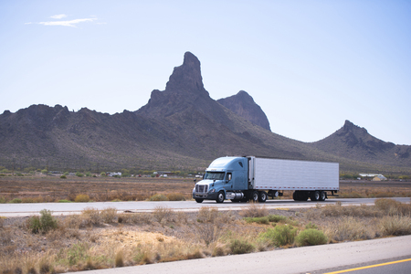Fresh popular professional big rig semi truck with a reefer trailer moving on the divided highway on a background of the famous mountain ranges bizarre in Arizona.