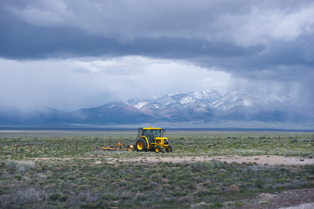 american field service: Yellow tractor with a plow working in the field in the middle of Nevada, cultivating land for growing food plants, framed by a ridge of high mountains covered with snow and drowning their tops in blue-gray cumulus clouds. Stock Photo