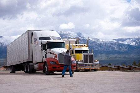 The truck driver goes to his bright yellow attractive custom tuning a big rig semi truck parked in the parking lot on a picturesque backdrop of snow-capped mountain ranges.