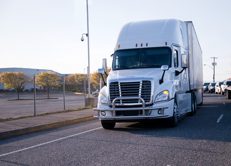 freightliner: New popular reliable big rig semi truck with bumper protective grille is moving in heavy traffic with other cars on urban city road. Stock Photo