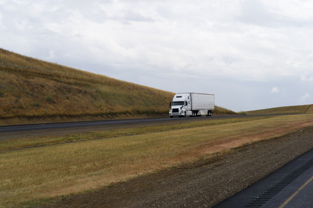 demanded: White demanded a popular model among drivers big rig semi truck delivers in reefer trailer the goods passing on California highways with little yellowed hills along the road.