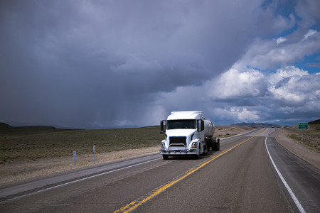 shipper: Modern popular comfortable semi truck with a cargo of liquid in the tank trailer carrying out flight on fuel delivery to the customer by road passing in the middle of the desert plains against a dark cloudy stormy sky Stock Photo