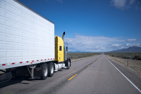 Yellow powerful classic big rig semi truck with high exhaust pipes pulls refrigerated trailer intended for the transport of perishable and frozen goods over long distances, transporting goods by leaving the horizon straight Nevada road