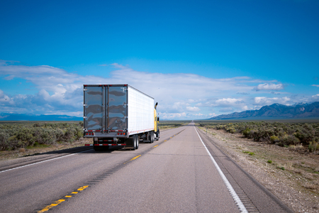 Yellow powerful big rig semi truck with refrigerated trailer running on the oncoming traffic line, overtaking vehicles in the other lane, clearly visible on the stretch of road on a flat plateau of Nevada with blue sky Banque d'images