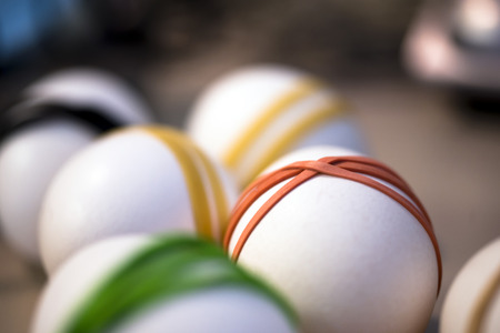 Multi-colored elastic bands put on white Easter eggs for the subsequent application of decorative paints and obtain an excellent handmade decoration accents to the Easter table.