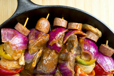 dietetics: Delicious kebabs from natural organic ingredients with marinated pieces of meat, fresh vegetables and sliced sausages strung on wooden skewers - a perfect dish ready for cooking on fire Stock Photo