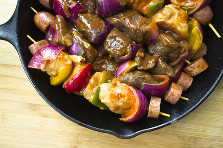 The culinary art of cooking healthy and tasty food presented a full pan of selected beef kebabs, sausages and fresh vegetables with spices, ready for roasting on the fire and served for dinner Stock Photo