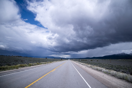 endless road: Stormy sky with heavy clouds and the endless road passing among expanses of prairie Nevada meet on the horizon, creating a single picture steppe landscape Stock Photo