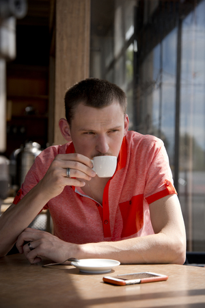 Young man with short hair in a red shirt drinking flavored coffee from a small cup while sitting at a wooden table in a sunlit window Stock Photo