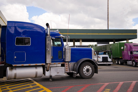 Blue classic American powerful heavy big rig semi truck with chrome accents is moving across the truck stop parking lot with a colored road markings and standing at rest semi trucks.
