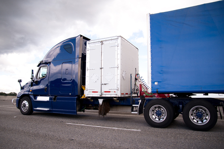 distances: The blue big rig American bonneted model of professional semi truck with a box compartment container on the frame and a covered trailer for the transport of industrial goods over long distances