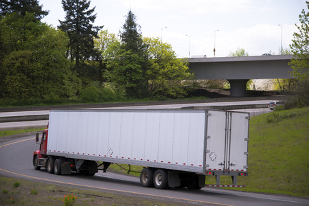 transport truck: Heavy Duty powerful red big rig semi truck with day cab for local cargo carry long dry van trailer turns on the highway from another highway exit with bridge surrounded by green trees