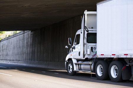 White powerful professional big rig semi truck for local regional transportation transports cargo with dry van trailer on a highway under the concrete bridge with shadow on the side wall