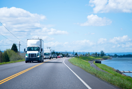 White big rig semi truck with day cab and top spoiler for regional transportation of commercial cargo moves along the straight road along the river in front of the column of other transports traffic