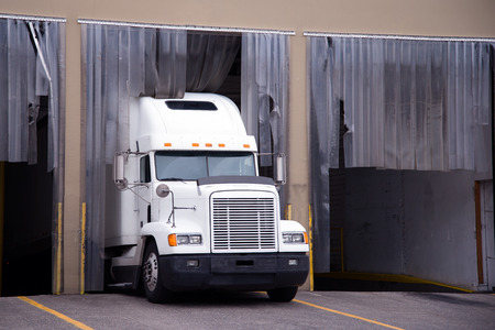 shipper: Old white classic big rig semi truck is unloaded at the warehouse dock for refrigerated trailers with consignments strict temperature cooling mode and protective cut strips at top of gates.