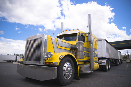 The classic yellow powerful American heavy big rig semi truck with chrome accents and individually designed customized truck body moving in a truck stop parking lot with two bulk trailers on background of cloudy blue sky.