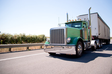 Classic American bonneted large green rig semi truck with high stylish chrome exhaust pipes transporting commercial cargo in bulk container trailer on the highway with trees behind the safety fence Stock Photo