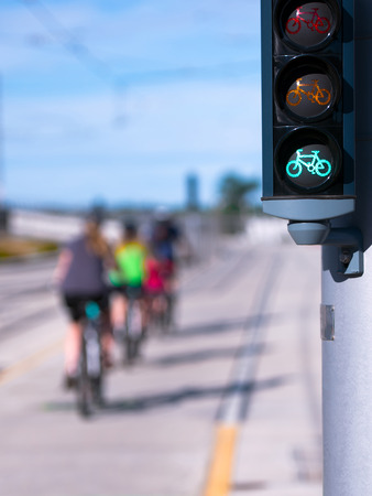 Green traffic light specifically for cyclists authorizing the movement of moving one by one on a flat straight road on their own bikes