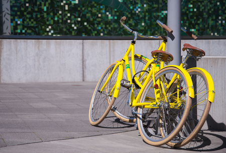 inseparable: Two bright yellow bike stand next as an illustration of common interest and affection of two loving people spending the weekend Stock Photo