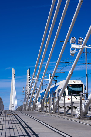 conection: Modern city tram runs along the bridge with cable extensions Willamette across the river in Portland with a shadow from fence of the bridge