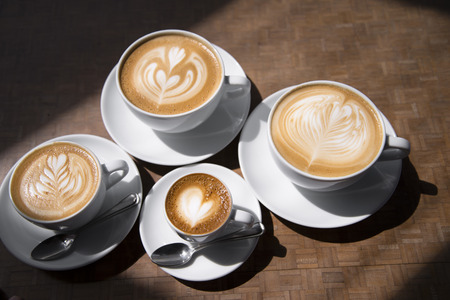Cups of coffee with different sizes from small to big for the entire family, on a saucer with a spoon with professional unique caramel designs on the foam in the form of hearts and plant design, view from above
