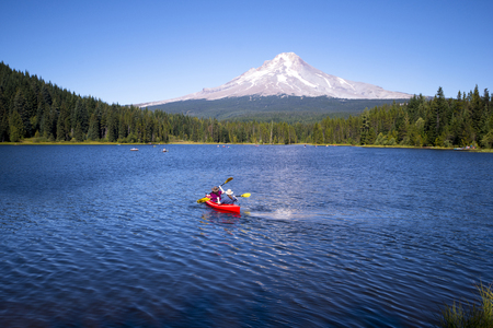Couple wearing hats active resting outdoor on the beautiful Trillium Lake recreation, rowing on the red kayak towards the high snowy Mount Hood, at the foot of which stretches of green forest creating a quiet lagoon that makes the rest on the lake unforge
