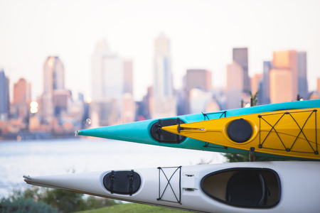 await: Colorful kayaks await their passengers on the background of high-rise office and residential buildings in down Town of Seattle, located on the opposite shore of the Pacific Ocean Bay Stock Photo