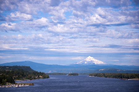 Panorama of Columbia River with forest banks and the marina, with a wavy blue water and the mountains on the horizon, which sticks out above the snow-covered Mount Hood, resting against a cloudy blue sky.