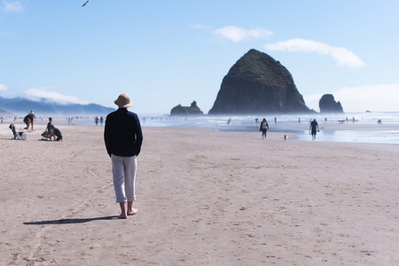 Young man in a hat with his hands in his pockets walking along the sand flat shores of the Pacific ocean breathing clean fresh sea air and thinking about the meaning of life and its transience, looking at forever standing rock in the ocean.