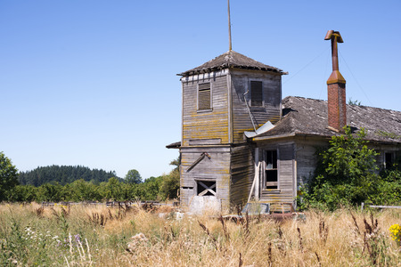 tower house: Old abandoned wooden residential house with tower and chimney with no windows and a leaky roof on an abandoned property with dry grass and rusty cars in the yard
