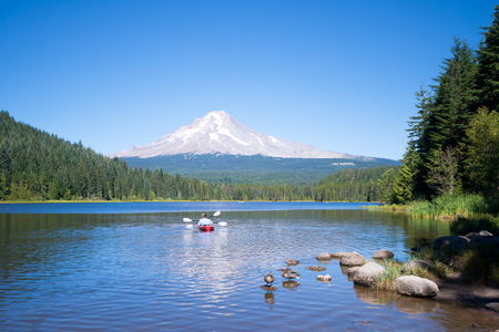 Picturesque idyll at Trillium Lake, the water that glides red canoe with oars - amateurs, and frolic ducks, reflected in the calm water, with almost bald snowy Mount Hood and slim green old trees unspoiled forest. Stock Photo