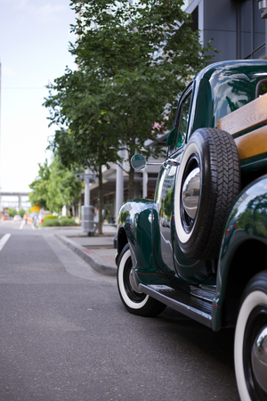 bodywork: Dark Green vintage old truck with a small bodywork, decorated by stained wood piece standing on a long street of a modern city - a great copy for any collector and connoisseur of retro cars