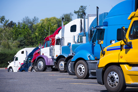 Modern trucks of various colors and models are involved for the transportation of different kinds of commercial goods are in a row on a truck stop in anticipation of the continuation of working flights for the delivery and transportation of industrial goo