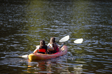 trillium: Young girls with oars rowing in the bright kayak on Trillium Lake, reflection of the sparkling green of the surrounding lake and forest patches of sunlight in shallow water wavy ripples - a great way to relax and devote their energies to the development o