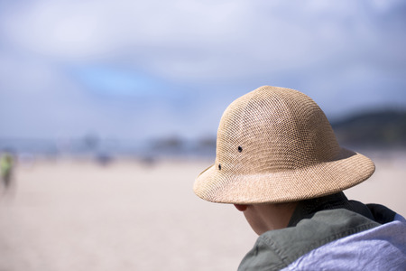 Young man in a protective hard braided woven straw hat is not the ocean sits and looks into the distance stretched coastal sand watching people relaxing on the beach to ensure their safety
