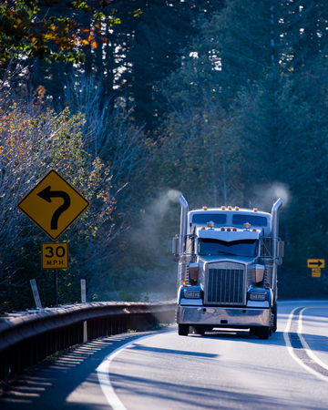 Huge blue classic big rig semi truck with chrome tailpipes highest of which is the smoke from the burned fuel the engine and semi trailer, turn on a winding road in the sunlight among the trees.