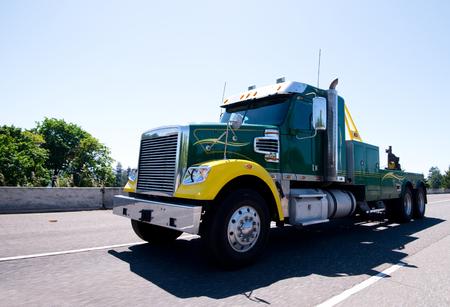 Nowoczesny kompaktowy pół ciężarówka do przewozu naczep ciężarowych podziale dużych platform wiertniczych, które potrzebują usługi holowania, z całego niezbędnego sprzętu i narzędzi z ruchów podnoszenia wciągarki na szerokiej autostradzie Zdjęcie Seryjne