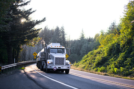 Large American professional powerful rig semi truck carries two fuel trailers tanks, or transporting liquid chemicals on the impressive winding road surrounded by green trees in sunny weather.
