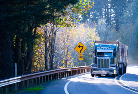 Large American professional powerful blue semi truck rig with a two trailers with high sides graft, carries loads on the winding road through the mountains, surrounded by yellowing autumn trees illuminated by the bright sun.
