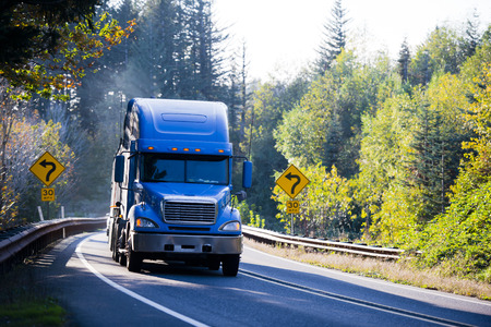 Large American professional powerful big rig semi truck with a flat bed trailer, transports goods on the winding road through the mountains, surrounded by yellowing autumn trees illuminated by bright sunshine, with road signs on both sides of the road.