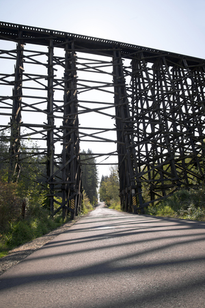 randomly: High strong old centenarian incumbent railway bridge constructed from stacked wooden beams intricately intertwined in a set of triangles, forming a randomly arranged pile of wooden elements. The miracle of engineering. Stock Photo