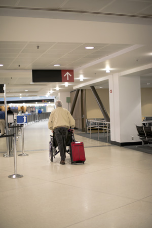 A man pushes a wheelchair and carries a red suitcase through the lobby of a modern airport with pointers and waiting room, following the passage of the gates for security control.