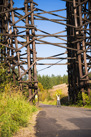 High current hundred years old railroad bridge across the valley through which the road passes, constructed of wooden logs as supports and beams joined together to form countless triangles for stability. Stock Photo