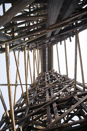 randomly: High old centenarian incumbent railway bridge constructed from stacked wooden beams intricately intertwined in a set of triangles, forming a randomly arranged pile of wooden elements. The miracle of engineering. Stock Photo