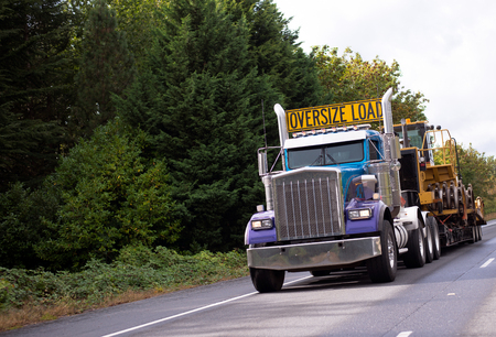 The big powerful rig semi truck with a sign Oversize load on the cab roof and special flat bed trailer which transports a large construction equipment on a straight interstate road Banque d'images