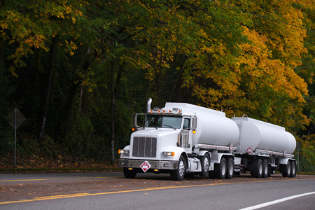 Modern white day cab semi truck with chrome grille and two tanks trailers going by straight multy-line road carry fuel gas cargo for safety delivery on background of yellowing autumn trees.