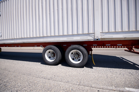 durability: Modern classic container semi trailer with corrugated walls for durability on the long orange metallic flat bed platform with dual wheels and tandem axles to adjust and weight distribution according to valid transportations standards on the American roads