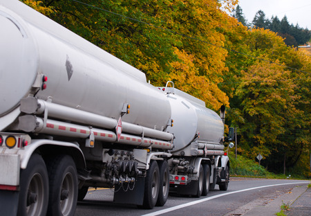 Modern big rig semi truck pulling two white tank trailers with combustible material along a scenic winding road with autumn yellowing trees